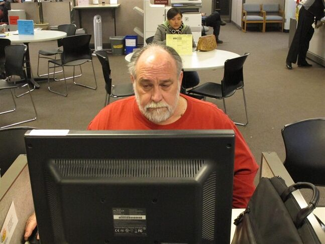 FILE - In this hursday Dec. 26, 2013 file photo, Richard Mattos, 59, looks for jobs at a state-run employment center in Salem, Ore. The Labor Department reports on the number of Americans who applied for unemployment benefits last for the last week of 2013 on Thursday, Jan. 2, 2014. (AP Photo/Jonathan J. Cooper, File)
