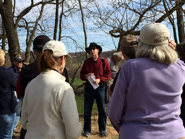 In this Sunday, April 6, 2014 photo, Keith White, center, leads a group of friends on a tour of the Monocacy National Battlefield south of Frederick, Md. The battle, which took place on July 9, 1864, is credited with delaying the Confederate move toward Washington, D.C. There are more than 300 miles of trails to explore in the 24 national parks designated as sites of significant Civil War battles. (AP Photo/Carole Feldman)