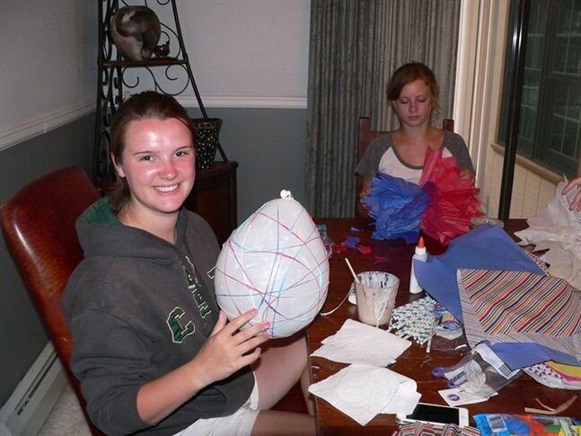This Thursday, July 3, 2014 photo shows Hope Clarke, 16, left, as she wraps yarn soaked in craft glue around a balloon while Hadley Hagemann, 16, works on a giant tissue pom-pom at a crafting night hosted at Clarke's house in Arvada, Colo. After the glue dried, Clarke popped and removed the balloon to reveal a colorful orb for hanging. Crafting encourages creativity, develops imagination and counters the many hours teens spend on their computers, phones and other