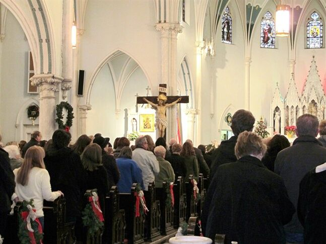 "This Jan. 12, 2014 photo shows people gathered for mass inside Our Lady of Perpetual Help Church in Buffalo, N.Y., during a ""Mass Mob."" Borrowed from the idea of flash mobs, Mass Mobs encourage crowds to attend Mass at a specified church on a certain day to fill pews, lift spirits and help financially some of the city's oldest but often sparsely attended churches. (AP Photo/Carolyn Thompson)"