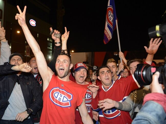 Montreal Canadiens fans celebrate their team's NHL playoff win over the Boston Bruins in Montreal Wednesday May 14, 2014. Montreal's Bell Centre was a sea of red, white and blue on Wednesday night as Canadiens fans packed the arena to watch their beloved Habs play 500 kilometres away.THE CANADIAN PRESS/Ryan Remiorz