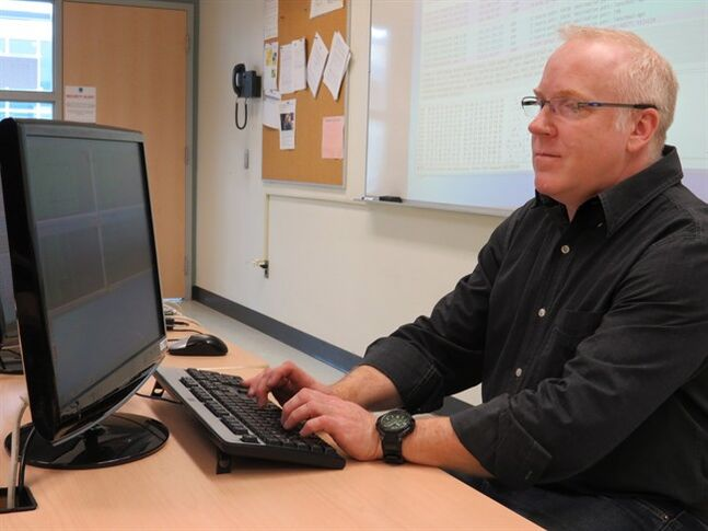 John Zabiuk, an ethical computer hacker, works away in his classroom at the Northern Alberta Institute of Technology in Edmonton on Feb. 14, 2014. THE CANADIAN PRESS/Dean Bennett