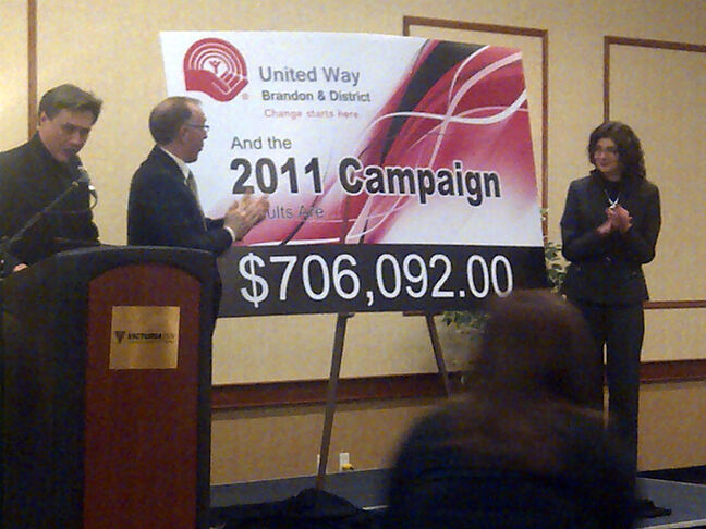 Fundraising campaign chairman Kevin Martin, centre, unveils the 2011 fundraising total as Frank McGwire (left) and board chair Trudy Corbett (right) look on.