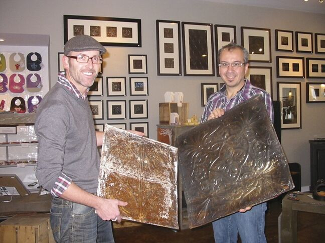 Tyler Kilkenny, left, and Todd Sawyer display old tin salvaged from abandoned farm houses that Kilkenny will turns into art pieces. The art works are on display in a gallery at TinHouse Coffee house, that Kilkenny and Sawyer recently opened in Russell.