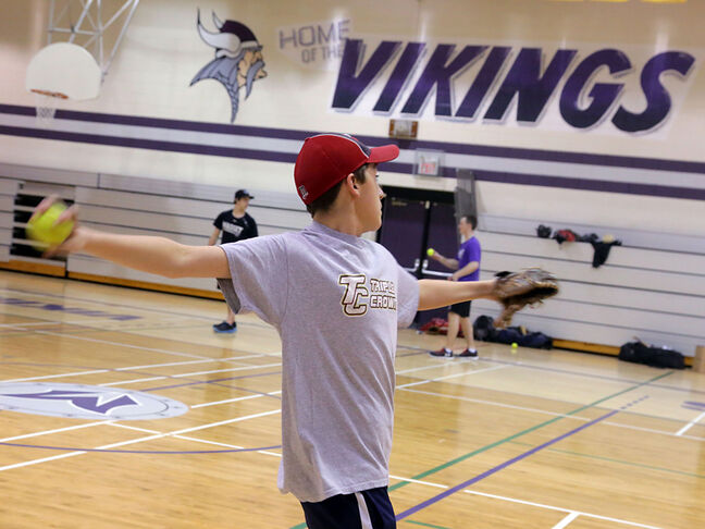Rookie Nolan Templeton tosses the ball during the Vikings' indoor baseball practice on Monday afternoon.