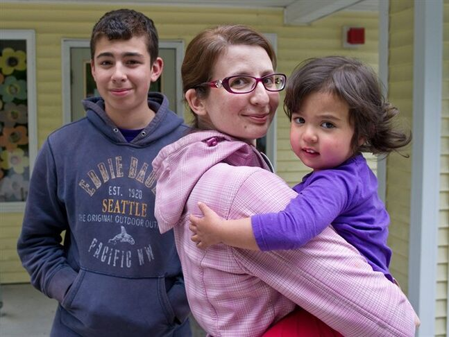 Lisa Flores poses with her daughter, Viviana, 2 and son, Dominic, 15, on Thursday, June 5, 2014, in Juneau, Alaska. Flores recently changed her daughter's middle name to Awesome with some persuasion from Dominic. (AP Photo/The Juneau Empire, Michael Penn)