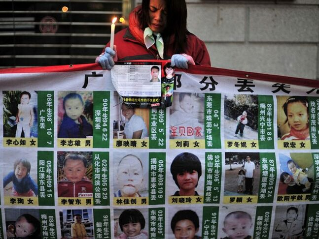 FILE - In this Jan. 24, 2010 file photo, a woman holds a candle behind a board showing photos of missing children during a campaign to spread the information to search for them in Wuhan, in central China's Hubei province. Chinese police have rescued 382 abducted babies and arrested 1,094 suspects in a national operation that busted four major Internet-based, baby-trafficking rings, the Public Security Ministry said Friday, Feb. 28, 2014. (AP Photo, File) CHINA OUT