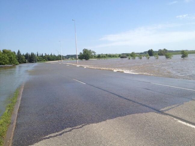 The Assiniboine River pours over the northbound lanes of First Street North in Brandon on Friday morning.