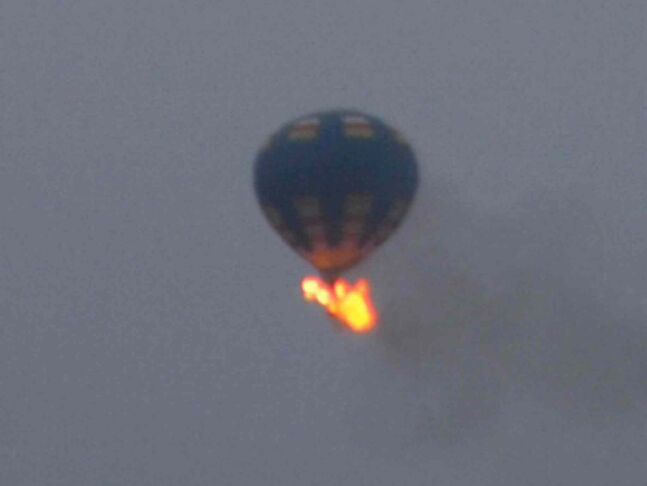 This photo provided by Nancy Johnson shows what authorities say is a hot-air balloon that was believed to have caught fire and crashed in Virginia, Friday, May 9, 2014. Virginia State Police received calls of the crash shortly before 8 p.m., police spokeswoman Corinne Geller told a news conference. Geller said a pilot and two passengers were believed to be on board, and that police believe it was the gondola that caught fire.
