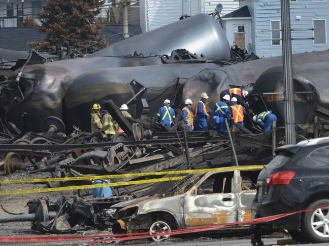 In this July 6, 2013 file photo, emergency workers examine the aftermath of a train derailment and fire in Lac-Megantic, Quebec. Forty-seven people were killed.