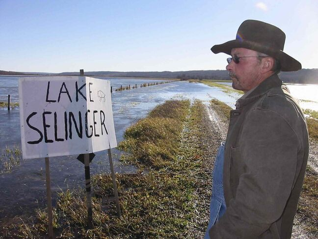 Farmer Gene Nerbas in front of fields flooded by the Shellmouth Dam and Shellmouth Reservoir, where someone placed a Lake Selinger sign.