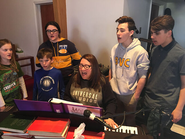 Seamus Malcolm, Aaron Cox, Kennedy DeBeer, Tyson Dornn and Deacon Bessant practice their vocals while Katherine Sherris, Mecca Productions' music and choir director, plays the piano.