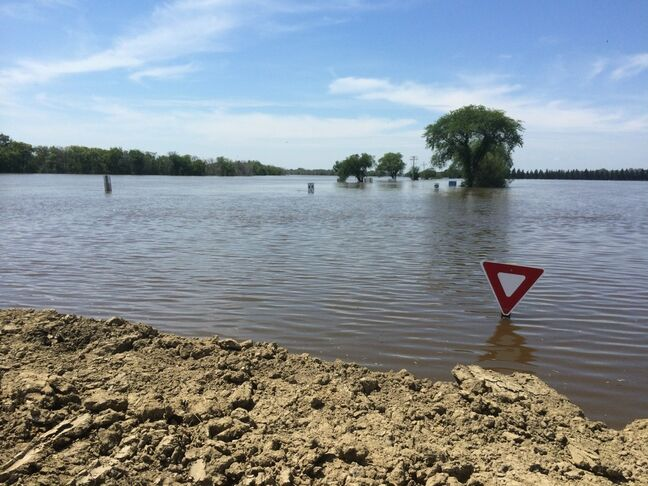 The Assiniboine River completely engulfs Grand Valley Road just west of 18th Street North in Brandon, as seen on Saturday afternoon from the top of the clay dike.