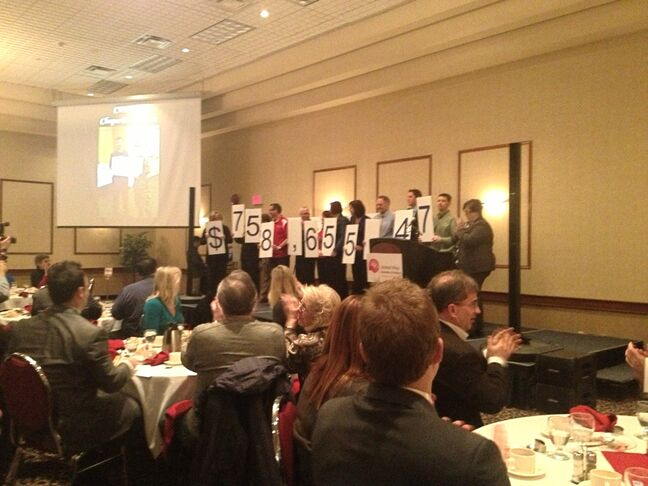 Members of the United Way show off the total fundraising amount from their 2012 campaign.