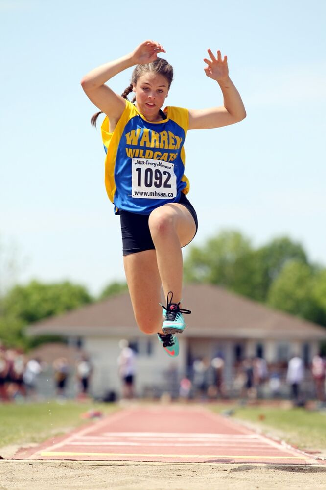 Grace Goodman of Warren Collegiate leaps through the air while competing in the Junior Varsity Girls Long Jump event on the opening day of the Provincial Track and Field Championships at the UCT Stadium on a scorching hot Thursday afternoon. (Tim Smith / Brandon Sun)