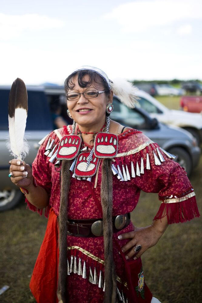 Gayle Pruden of Winnipeg holds a feather after asking for a photo during the Rolling River First Nation powwow on Sunday afternoon. (Tim Smith / Brandon Sun)