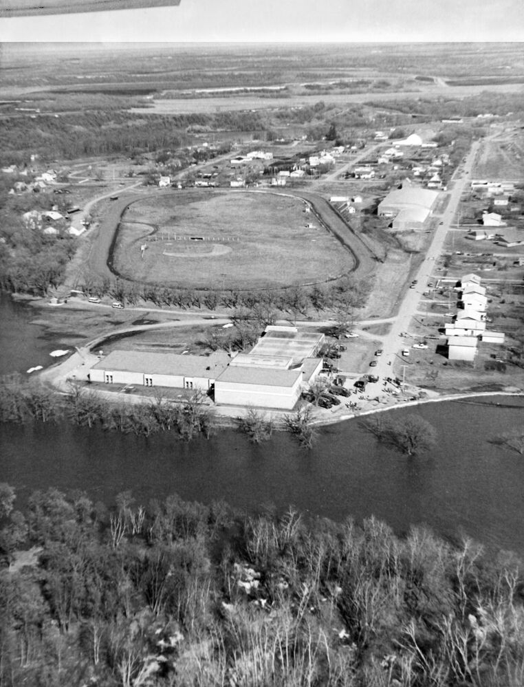 The town of Wawanesa was cut off by floodwaters in 1976. This aerial shot looks northeast at the fairgrounds, with Commercial Street on the right-hand side. (Brandon Sun archives, 1976)