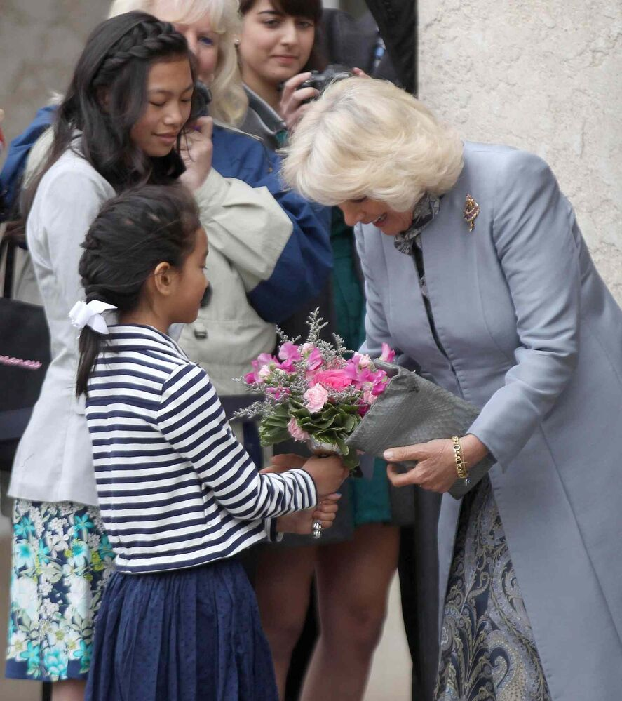 The Duchess of Cornwall  gets flowers from Meagan Gillis, 12 and her sister Jillian, 8 , as they leave the Assiniboine Park Pavilion Gallery. (JOE BRYKSA / WINNIPEG FREE PRESS)