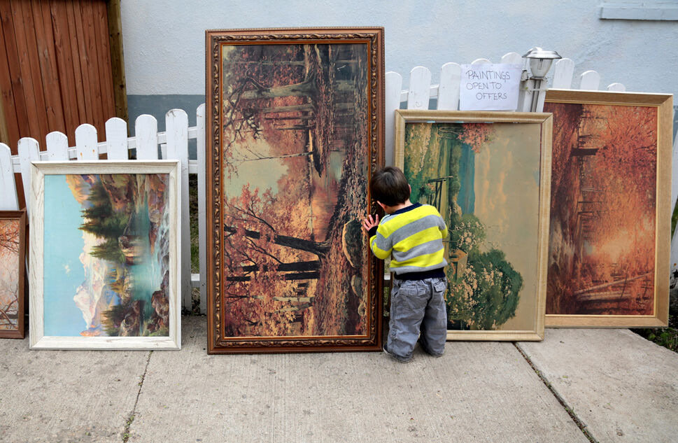 Ryan John Amyotte checks out some paintings at a yard sale on Douglas Street in May. (Colin Corneau/Brandon Sun)