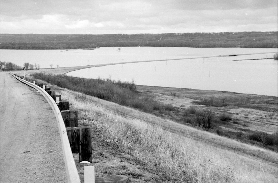 """The road is a thin strip of dry land, through a flooded-out valley. The precise location isn't certain. The image is from a roll of photos identified only as """"Kenton Lenore"""" from April 27, 1995. (Dirk Aberson / Brandon Sun archives)"""