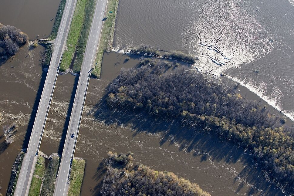 The Assiniboine River pours into farmland bordering the river banks at the Highway 1 bridge.