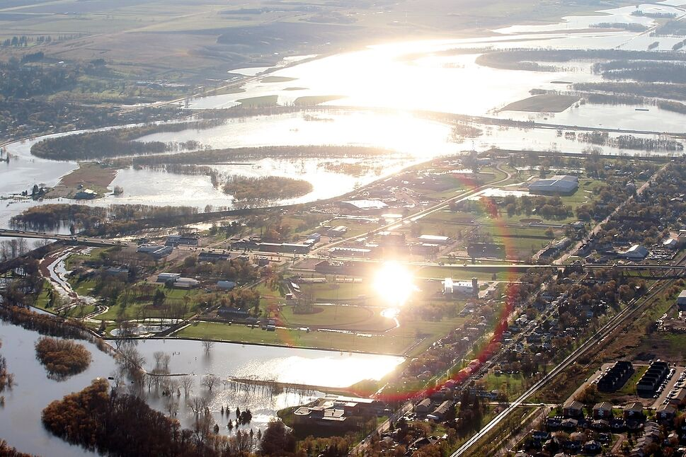 Sunlight reflects off of standing water near Brandon Fire Hall #1 as the sun rises over Brandon.