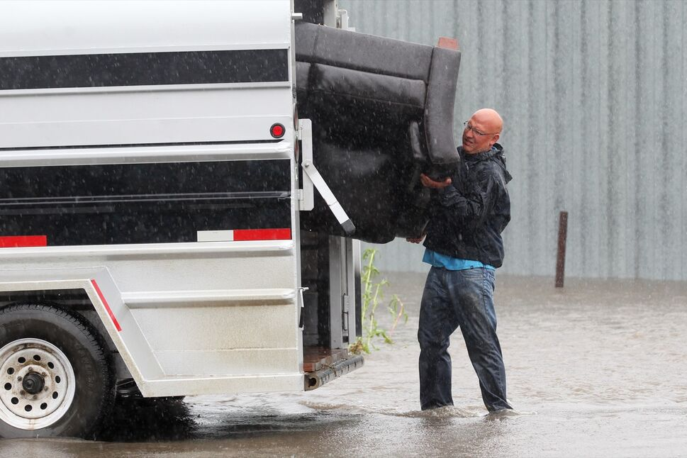 Greg Baerg loads a couch into a trailer on Sunday after the home he and his wife Amy live in in the village of Cromer in southwestern Manitoba flooded due to excessive rainfall over the weekend. The Baerg's are from Alberta but are living in Cromer while working in the area.  (Tim Smith/Brandon Sun)