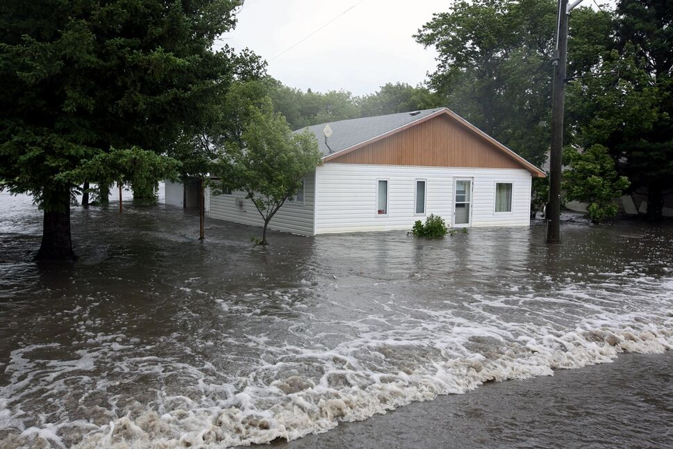 Water pours over Highway 256 and floods homes in the village of Cromer in southwestern Manitoba on Sunday after incessant rainfall over the weekend caused flooding forcing the evacuation of approximately 30 residents.  (Tim Smith/Brandon Sun)