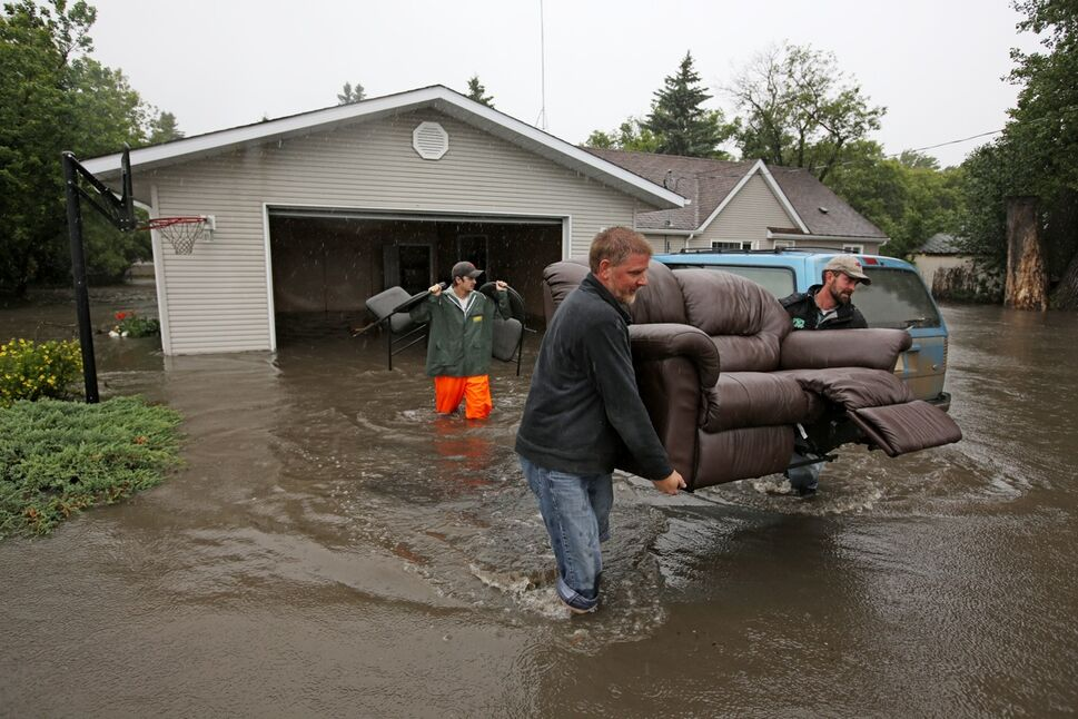 A Mr. Froese (no first name given) and Ivan Penner carry a couch from the home of Greg and Amy Baerg to a waiting trailer in the village of Cromer in southwestern Manitoba on Sunday after flood water inundated several homes in the small community and forced the evacuation of approximately 30 residents. (Tim Smith/Brandon Sun)