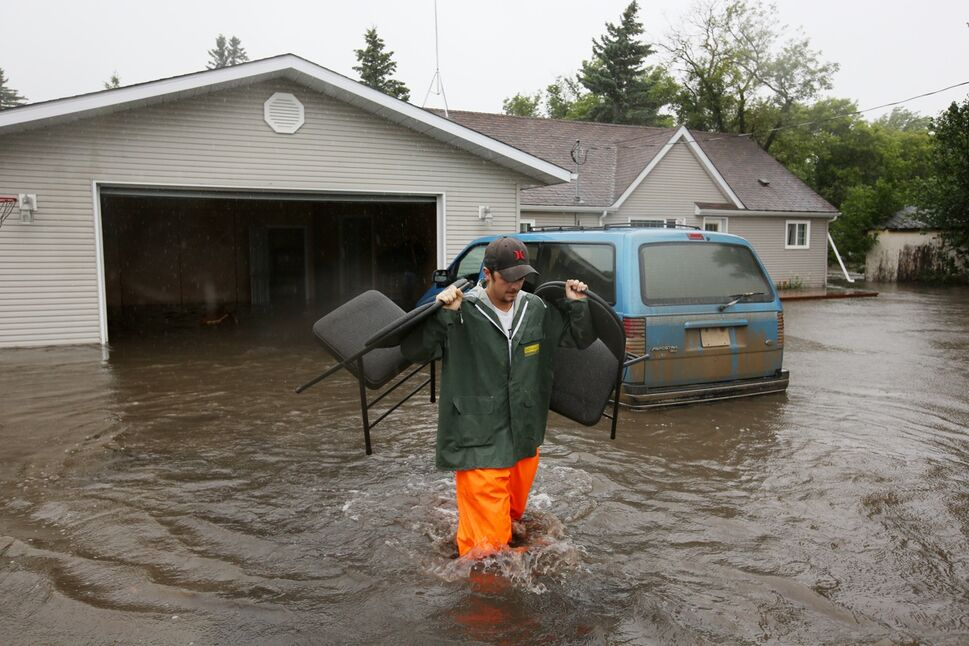 Christian Jeanes carries chairs out of his neighbours home to a waiting trailer while helping remove belongings from the flooded home in the village of Cromer in southwestern Manitoba on Sunday after incessant rainfall over the weekend caused flooding forcing the evacuation of approximately 30 residents. Jeanes now lives in Virden so his home next door was empty but is still heavily affected by the flooding.   (Tim Smith/Brandon Sun)
