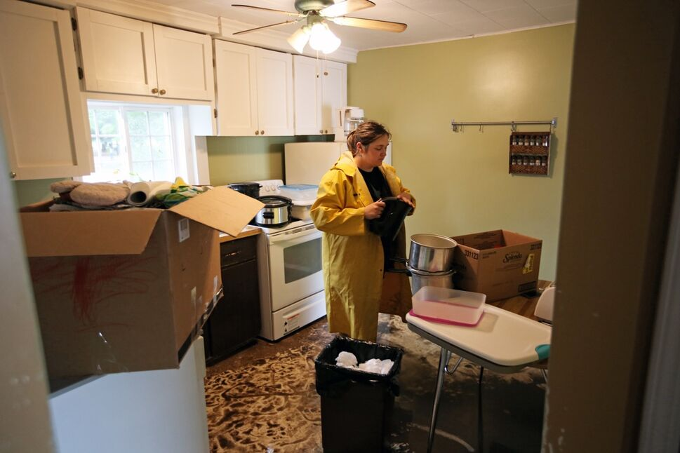 Ashley Feldman packs up belongings in the home of her neighbours Greg and Amy Baerg on Sunday after the home in the village of Cromer in southwestern Manitoba was flooded due to excessive rainfall over the weekend. Several homes in the small community were flooded and approximately 30 residents were evacuated.  (Tim Smith/Brandon Sun)