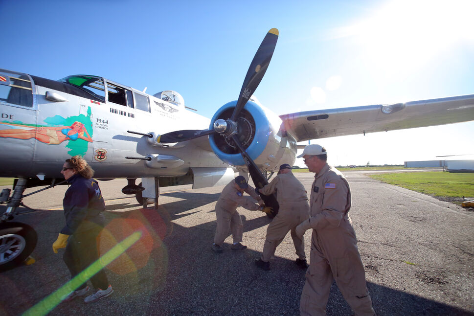 Brandon Sun Members of the flight ground crew for the Commemorative Air Force based out of Mesa, Ariz. rotate the blades of a propellar on a Second World War-era B-25J bomber on Tuesday morning, in preparation for a 10 a.m. flight.  (Matt Goerzen/The Brandon Sun)