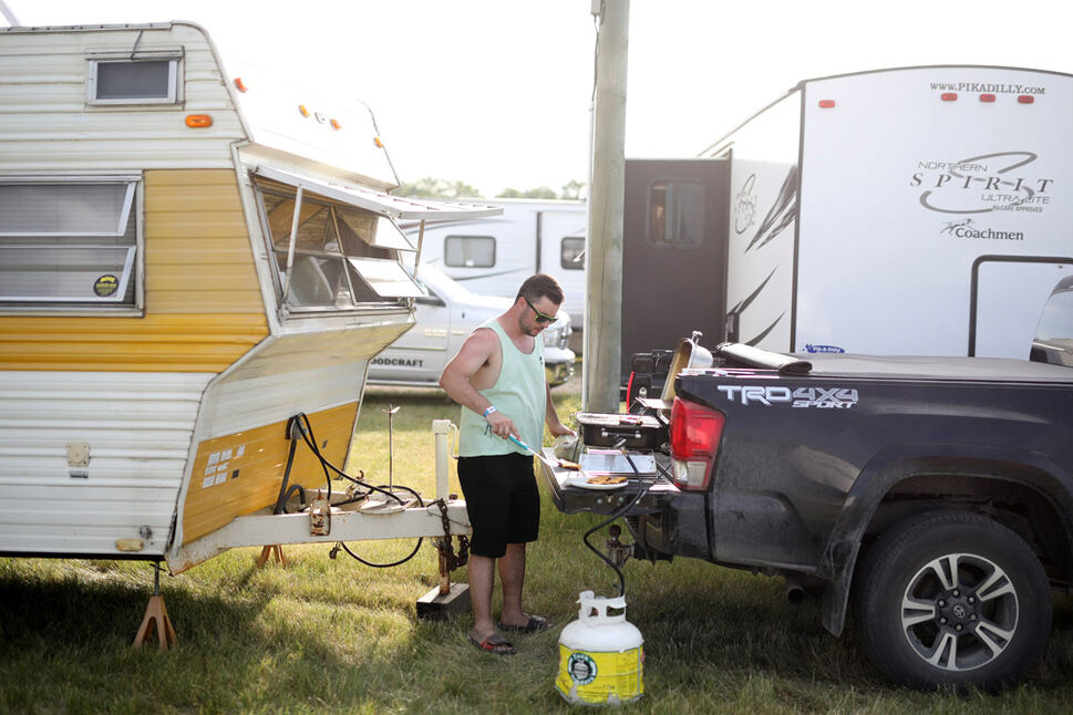 Jorry Holder of Brandon barbecues burgers on the tailgate of a truck during Dauphin's Countryfest 2019 on a scorching hot Friday evening. (Tim Smith/The Brandon Sun)