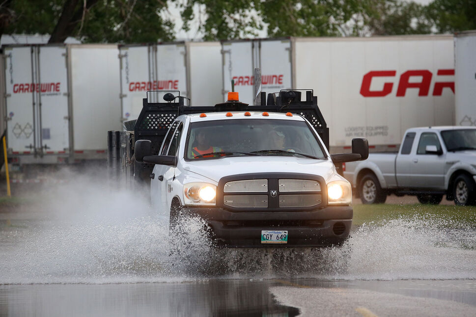 A truck plows through a large puddle on Park Avenue East, left over from storm systems that hit western Manitoba on Sunday. (Matt Goerzen/The Brandon Sun)
