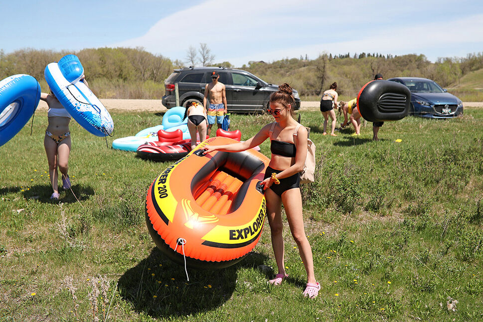 Eden Prawdzik waits for friends as they get ready to float down the Little Saskatchewan River at Kirkham's Bridge on a scorching hot Friday. (Tim Smith/The Brandon Sun)