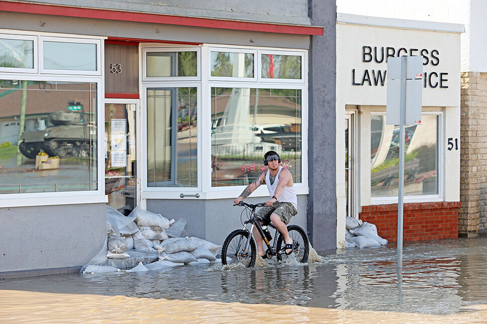 29062020 Jesse Hunt walks his bike through flood water inundating Main Street in Minnedosa on Monday after heavy downpours Sunday evening into overnight caused widespread flooding. The swollen Little Saskatchewan River overflowed into downtown Minnedosa flooding several businesses and residences. (Tim Smith/The Brandon Sun)