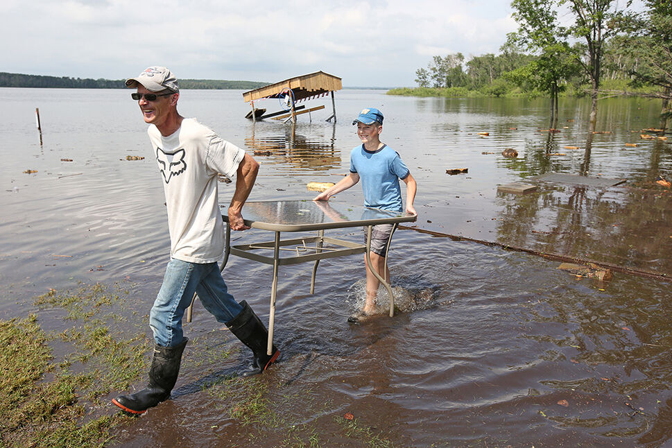 29062020 Steve Hamm and his son Andrew, 14, wade through floodwater from the swollen Lake Wahtopanah, aka the Rivers Reservoir, where there should be dry land while helping fellow campers at Jake Fast Park retrieve items from campers that were flooded on Monday after heavy downpours Sunday evening into overnight caused widespread flooding. Hamm's family's camper did not flood.  (Tim Smith/The Brandon Sun)