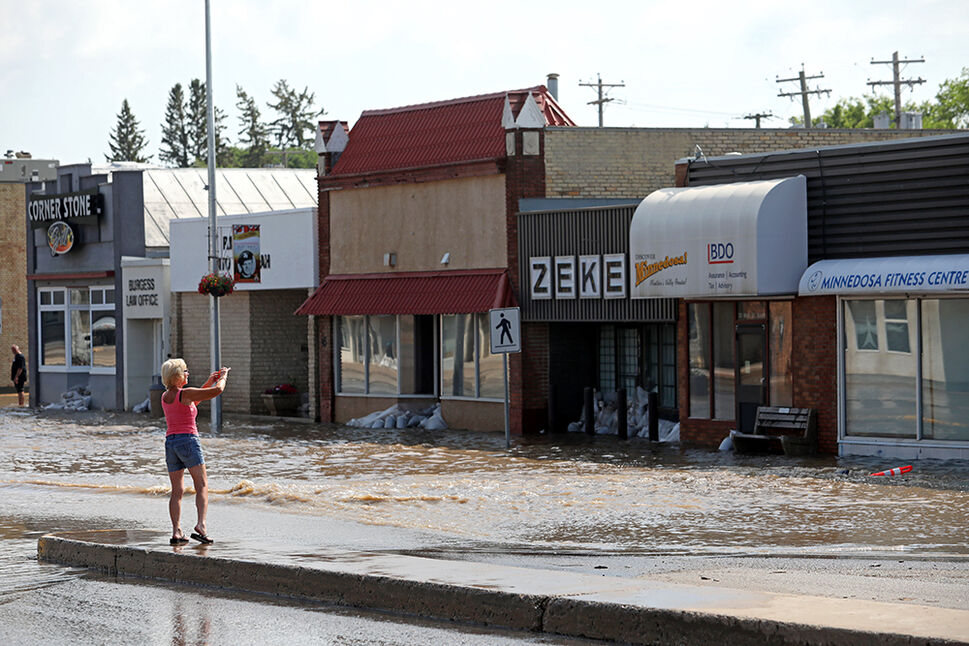 29062020 A woman takes a photo of the flooding on Main Street in Minnedosa on Monday after heavy downpours Sunday evening into overnight caused widespread flooding. The swollen Little Saskatchewan River overflowed into downtown Minnedosa flooding several businesses and residences. (Tim Smith/The Brandon Sun)