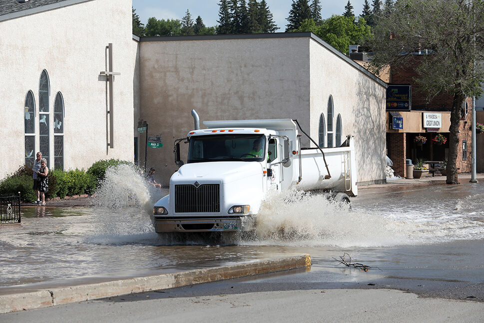 29062020 Vehicles pass through flood water on Main Street in Minnedosa on Monday after heavy downpours Sunday evening into overnight caused widespread flooding. The swollen Little Saskatchewan River overflowed into downtown Minnedosa flooding several businesses and residences. (Tim Smith/The Brandon Sun)