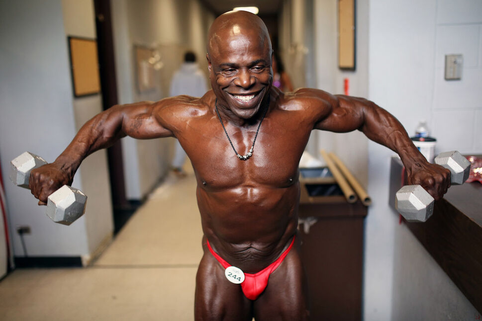 61-year-old Valentine Payne of Winnipeg lifts weights to pump up his muscles backstage prior to competing. (Tim Smith/Brandon Sun)