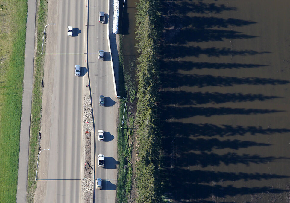 Trees bordering 18th St. in Brandon cast long shadows in the flood water as traffic passes by.