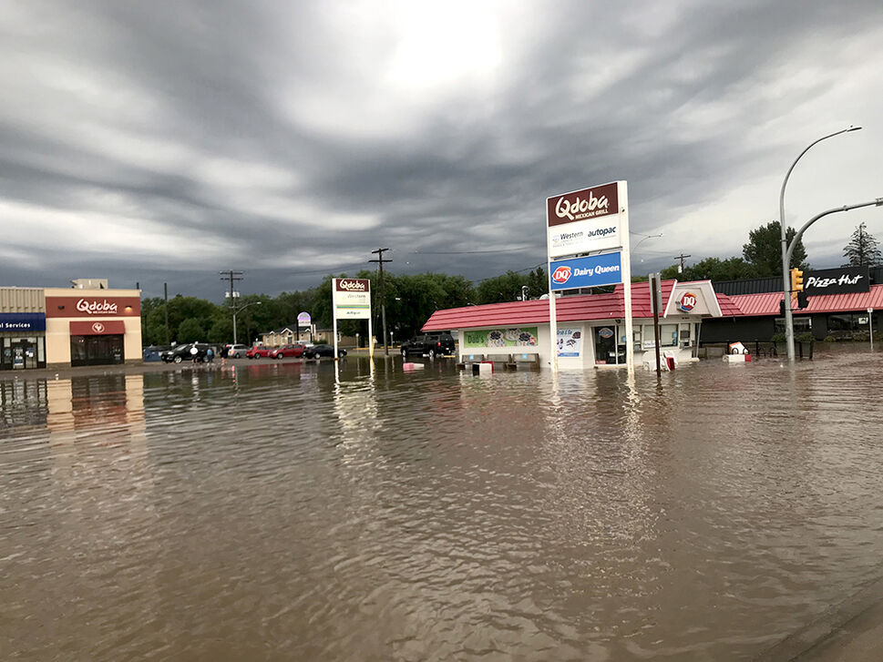 A massive puddle consumed the intersection and the mall parking lot at the corner of 18th Street and Park Avenue on Sunday evening following the storm. (Drew May/The Brandon Sun)