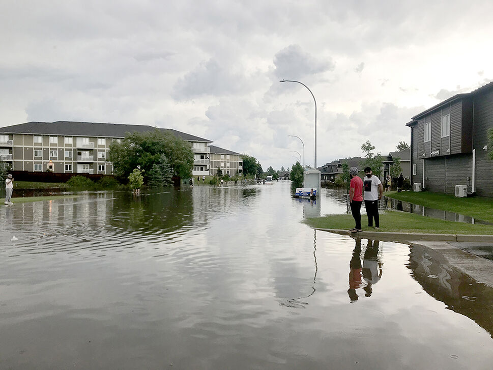 Several feet of water flooded Sycamore Drive on Sunday evening, rising up to some car doors and covering front lawns. (Drew May/The Brandon Sun)