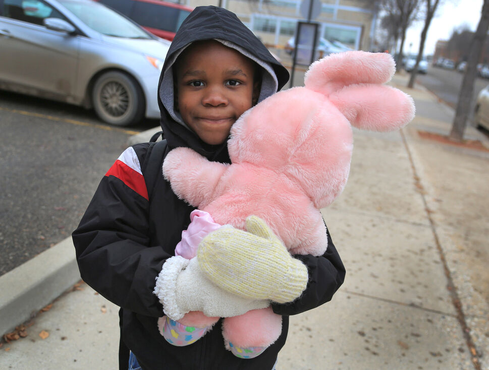 Samuel Enone holds his new toy rabbit as he makes his way along 11th Street in October. The young Nigerian immigrant picked up the toy with his mother on a shopping trip downtown. (Colin Corneau/Brandon Sun)