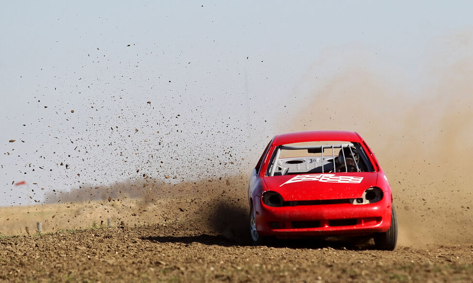 A car spits up dirt as it rounds a corner during a heat.