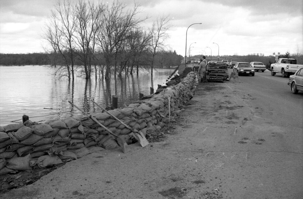 A wall of sandbags protects 18th Street North, at John Avenue, from the rising Assiniboine. The old Thompson Bridge can be seen behind the pile of pallets. (Dirk Aberson / Brandon Sun archives, April 25, 1995)