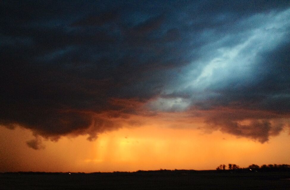 The setting sun makes a storm system glow as it rolls across the prairies west of Brandon on Thursday evening.