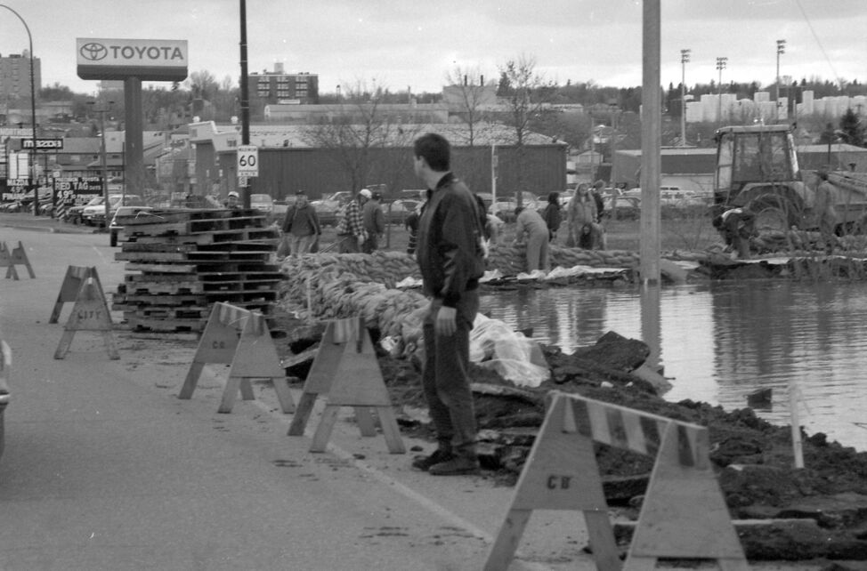Workers build up the sandbag dike at 18th Street North and John Avenue. (Dirk Aberson / Brandon Sun archives, April 25, 1995)