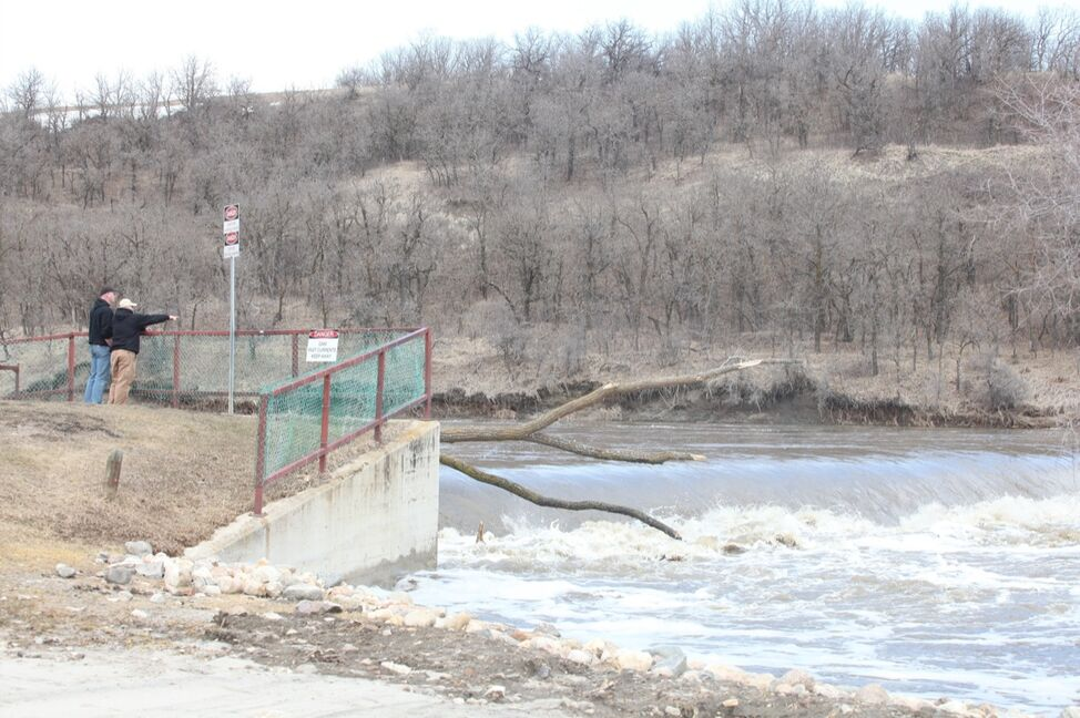 Onlookers watch as water from the swollen Souris River rages over the dam in Wawanesa on Monday.