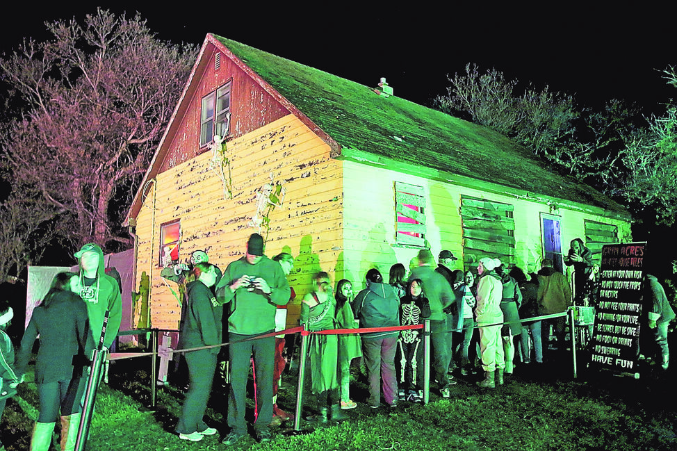 Visitors wait in line to enter the haunted house during the final day of the Grim Acres Scare Away Cancer fundraiser for the Canadian Cancer Society on Saturday night.